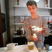 Thaddeus Fry flames an orange peel while preparing a butterscotch latte at Coat Check Coffee in the historic Athenaeum building off Mass Ave. Heat from the flames expresses citrus oils that bring out the spicy aroma and flavors of the specialty coffee drink, a favorite at the coffee shop.