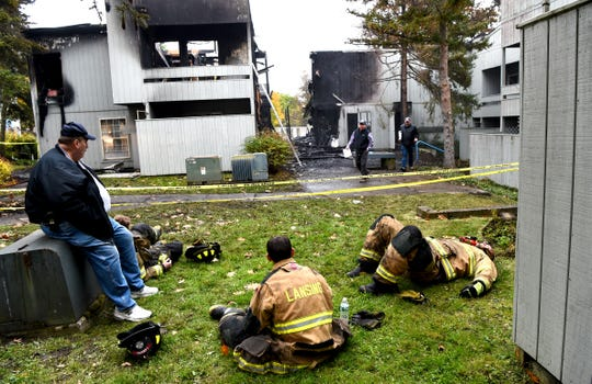 First responders (in foreground, from left to right) Zach Steiner, Dennis Griffin, Tyler Mix and Scott Walters remain on the scene of an overnight fire at University Park Apartments in Lansing. The Lansing Department arrived on the scene around 2 a.m. and remained through the morning as the building continued to smoke. October 22, 2019.