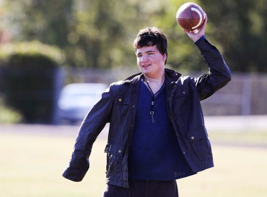 William Smith, one of the team managers for the North Oldham High School football team, tosses a football on the sideline during practice.