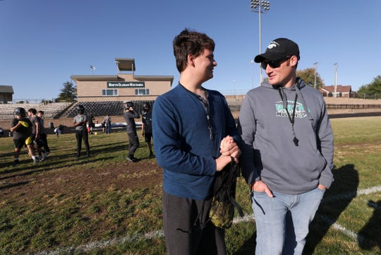 William Smith, left, one of the team managers for the North Oldham High School football team, chats with head coach Joe Gamsky during practice at the school in Goshen.