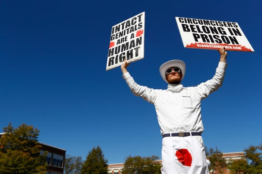 David Atkinson of the Bloodstained Men holds signs decrying the use of circumcision as the group protests male genital mutilation on the University of Memphis campus on Tuesday, Oct. 22, 2019. Ten members of the group who are traveling the South, joined a few local volunteers to spread their views in Memphis, one of 16 cities the group will visit.