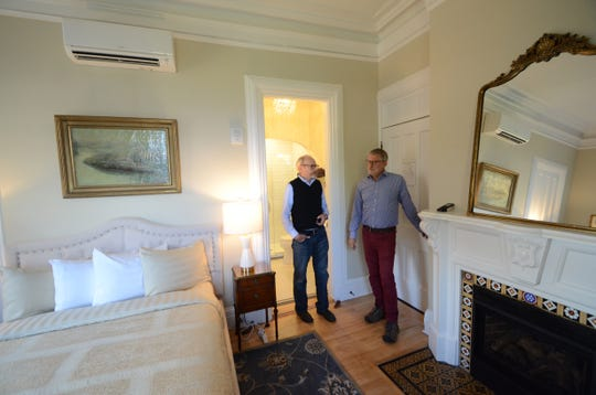 Governor's Mansion Inn owners David Waugh, left, and Bob Klebba discuss the life of Norwegian violinist Ole Bull in the guest room that bears his name.