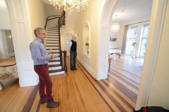 "Governor's Mansion Inn owners Bob Klebba, left, and David Waugh stand in the entryway of the hotel. The large room to the right is where the couple believe the Wisconsin Idea was hatched during the term of Gov. Robert ""Fighting Bob"" La Follette."