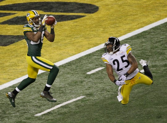 Greg Jennings (85) catches a pass for a touchdown a head of Pittsburgh Steelers defender Ryan Clark (25) in the first half, in Super Bowl XLV, in Arlington, Texas, Sunday, February 6, 2011.