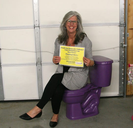 """Donna Forrester, director of Serenity Domestic Violence Support & Shelter tries the """"Purple Potty"""" on for size. The Purple Potty started humorous way for the shelter to raise funds during the month of October, which is National Domestic Violence Awareness Month. Over the years, Twin Lakes Businesses have parlayed the potty's appearance to raise additional funds for the shelter, and use it as a marketing gimmick for their own business."""