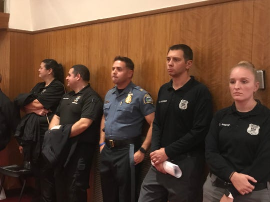 Boonton Police Chief David Mayhood, center, stands in the back of the auditorium with his dispatchers, not long before their jobs were eliminated by the board of alderman, which voted to transfer dispatch to the county 911 system during a heated meeting at Boonton High School. Oct. 22, 2019.