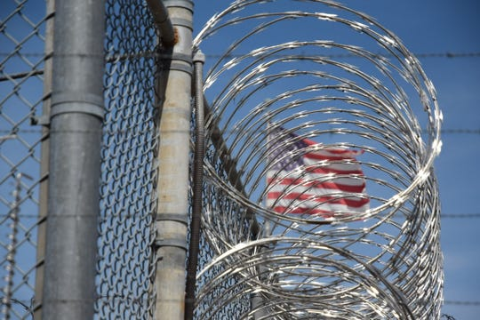 The American flag seen behind barbed wire at Holman Correctional Facility on Oct. 22, 2019.