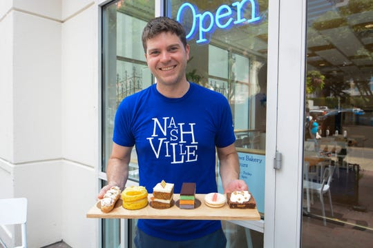 Chef and owner David Andrews displays his Mixed Berries-Cream Éclair, Orange-Almond Cake, Carrot Cake, Rainbow Cake, Macaron, Jack Daniels Honey Brownie at D'Andrews Bakery and Café