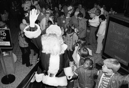 With eager children following him, Santa Claus heads to his chair at the 100 Oak Shopping Mall Nov. 25, 1983.