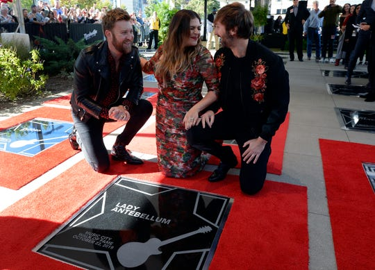 Charles Kelley, left, Hillary Scott, and Dave Haywood of Lady Antebellum pose by their star on the Music City Walk of Fame during an induction ceremony on Tuesday.