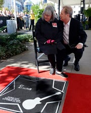 Merle Atkins looks at the star for her brother, Chet Atkins, with Steve Wariner on the Music City Walk of Fame.
