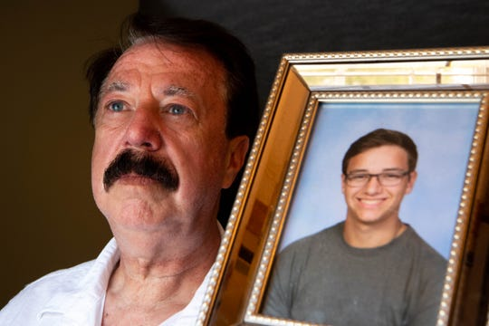 David Smith poses for a portrait with a photo of his son, Channing Smith at his home Friday, Oct. 11, 2019, in Manchester, Tenn. Channing died by suicide after sexually explicit messages between him and another boy were leaked.