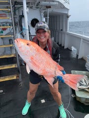 Palmetto Ridge High School marine teacher Kathy Schroeder, 48, holds a red snapper while conducting a longline survey aboard the Oregon II as part of NOAA's Teacher at Sea program.