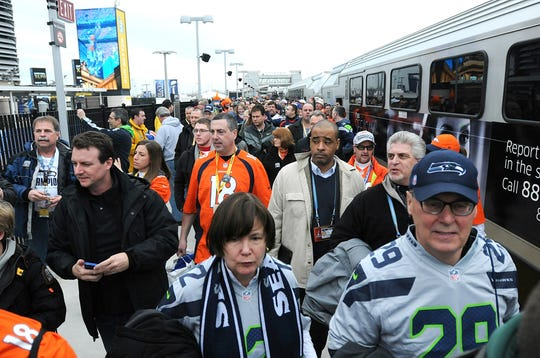 Passengers get off a NJ Transit train, which is the first train to arrive  at Meadowlands Station, on the way to the Super Bowl at MetLife Stadium in East Rutherford, February 2, 2014.