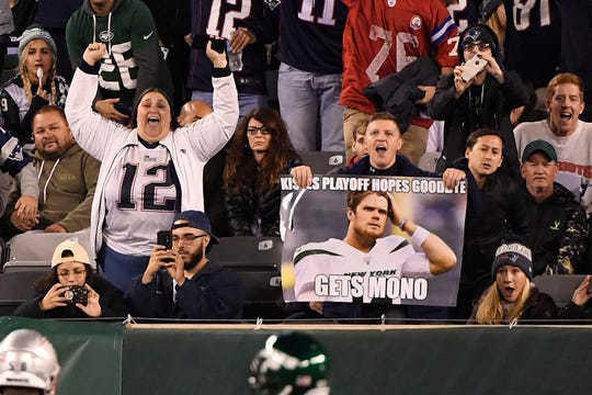 New England Patriots fans celebrate a interception thrown by New York Jets quarterback Sam Darnold (not pictured) in the second half. The New England Patriots shut out the New York Jets, 33-0, at MetLife Stadium on Monday, Oct. 21, 2019, in East Rutherford.