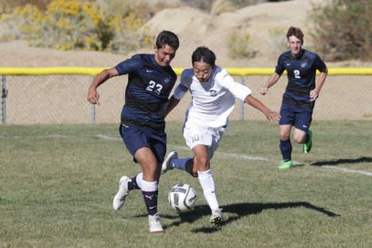 Piedra Vista's Logan Sewell and La Cueva's Roland Zhang battle for possession of the ball during Tuesday's District 2-5A boys soccer match at PVHS.