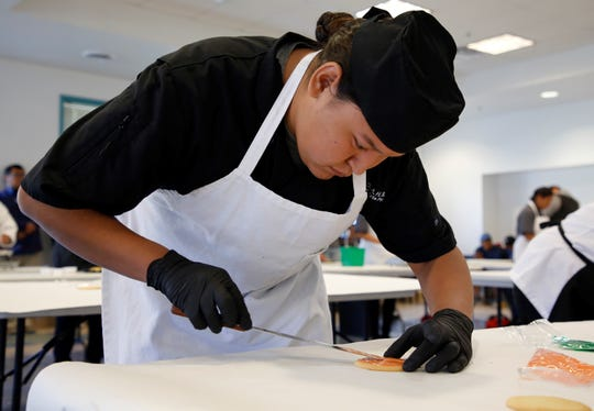 Dejaunrei Yazzie, a student at Greyhills Academy in Tuba City, Arizona, decorates a cookie during the baking competition at Skills Fest on Oct. 22 at Navajo Technical University in Crownpoint.