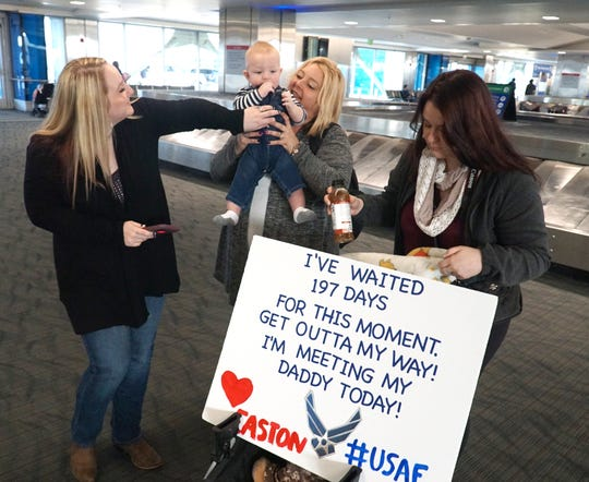 Alexis Halteman, left, awaits the return of her U.S. Airforce husband Kaleb at Metro's North Terminal on Oct. 22, 2019 with her mother Kristle Vann, center, holding Alexis' son Easton) and her sister Aubrey Ostrander, right.
