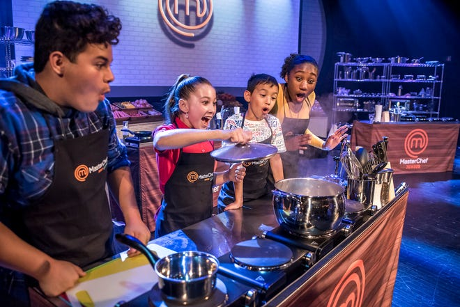 MasterChef Junior contestant Malia, second from left, opens a pot, as Evan, from left, Matthew and Jasmine look on during MasterChef Junior Live!