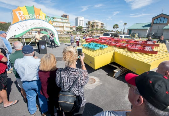 A small crowd gathers as Escambia County auctions off the old Pensacola Beach sign on Tuesday.