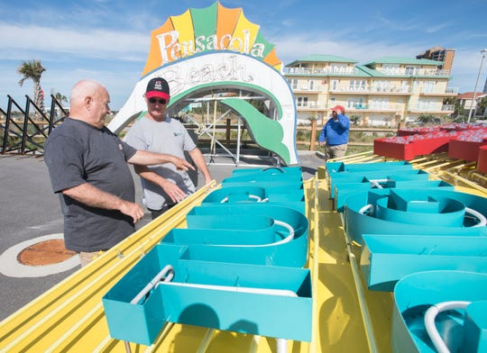 Gene Pehek, left, and Will Clause, of Gulf Breeze, check out the old Pensacola Beach sign before the auction Tuesday.