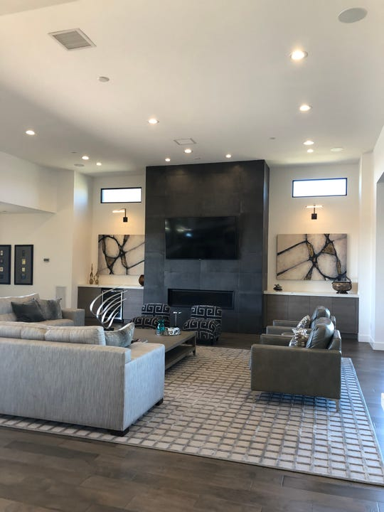 While the symmetrical design of the fireplace and furniture placement lend to the modern design, the plush rug and fabrics on the couch and pillows add warmth to the space.