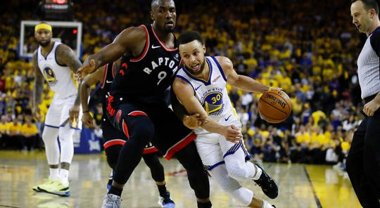 Warriors guard Stephen Curry tries to dribble past Raptors center Serge Ibaka during Game 3 of the NBA Finals on June 5.