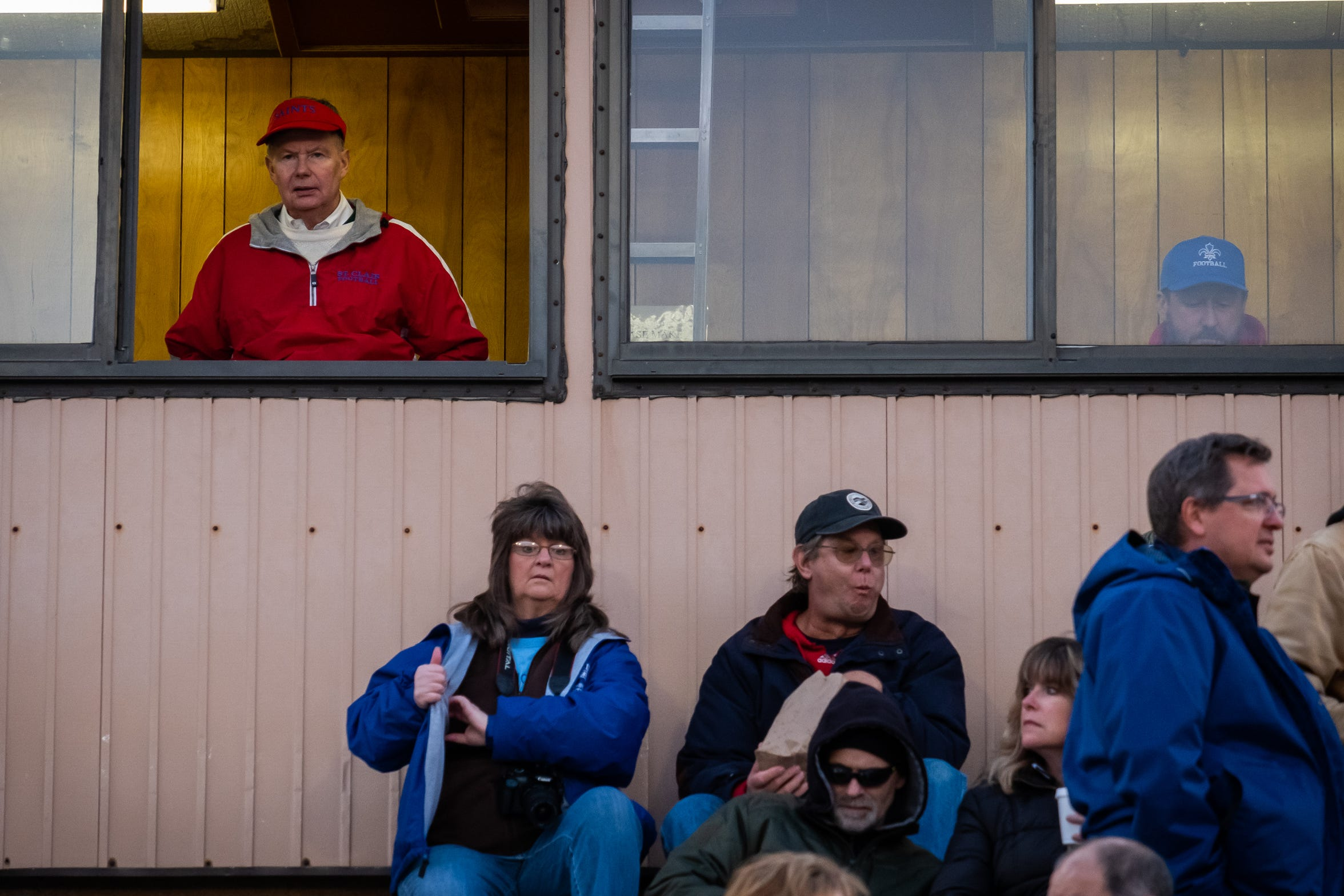 Bill Durow, 70, wears St. Clair High School attire as he watches the team warm up from the press box before taking on South Lake Friday, Oct. 18, 2019, at East China Stadium. Durow always wears the gear of whichever home team he's keeping time for.