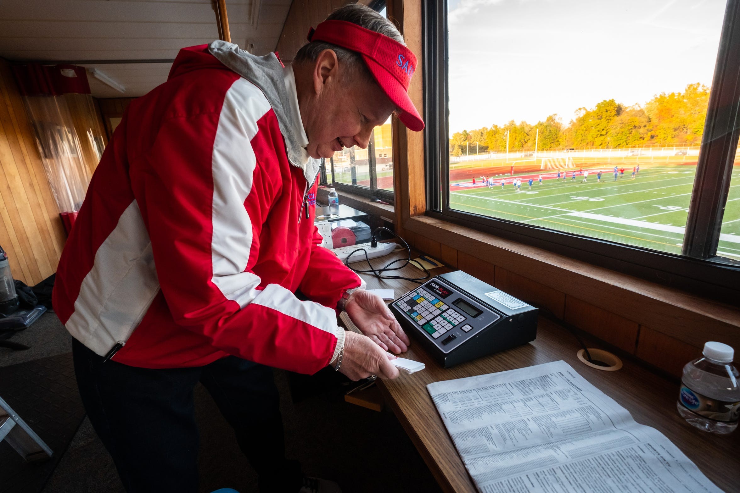 Bill Durow, 70, works to set up his space in the press box at East China Stadium before St. Clair takes on South Lake Friday, Oct. 18, 2019. Durow runs the scoreboard for St. Clair, Marine City and Cardinal Mooney football, St. Clair boys' and girls' basketball, SC4 men's and women's basketball and St. Clair and Marine City soccer.