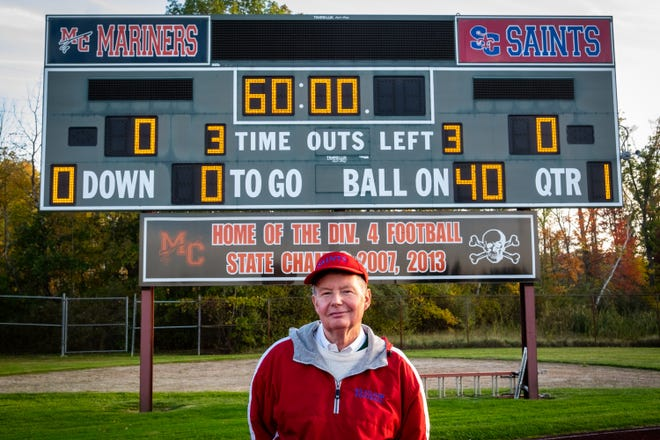 Bill Durow, 70, poses for a photo in front of the scoreboard at East China Stadium Friday, Oct. 18, 2019, ahead of St. Clair's game against South Lake. Durow taught for East China School District for 31 years and never missed a single day. He has worked the scoreboard for more than 700 home games for St. Clair, Marine City and Cardinal Mooney high schools. In addition, he works the scoreboard for St. Clair's boys and girls basketball, SC4 men's and women's basketball and St. Clair and Marine City soccer.