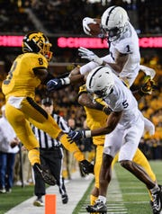 Oct 12, 2019; Iowa City, IA, USA; Penn State Nittany Lions wide receiver KJ Hamler (1) runs for a 22 yard touchdown reception from quarterback Sean Clifford (not shown) as wide receiver Jahan Dotson (5) blocks and Iowa Hawkeyes defensive back Matt Hankins (8) and defensive back Geno Stone (9) defend during the second quarter at Kinnick Stadium. Mandatory Credit: Jeffrey Becker-USA TODAY Sports