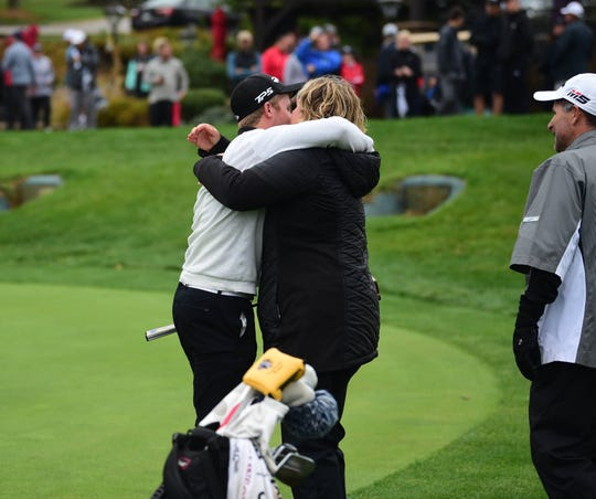Central York senior golfer Carson Bacha hugs his mother, Kerri, while his father, Kevin, looks on after clinching the 2019 PIAA Class 3A title