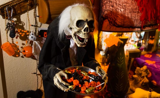 A skeleton butler with a tray of candy greets guests.