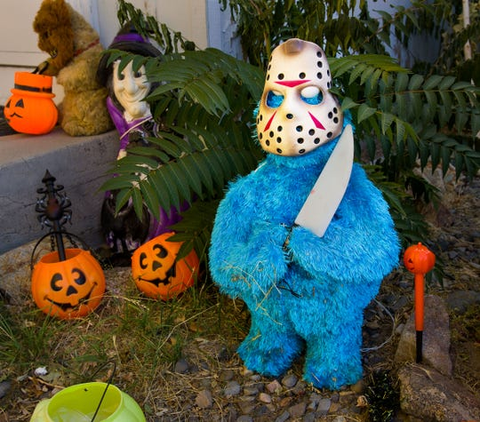 Cookie Monster wears a Jason mask and holds a fake knife near the front door of the Willard home.