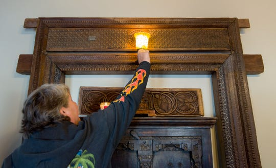 Katie Hasbrouck demonstrates how hard it is to turn a paddle socket light switch. The antique light fixture mysteriously turned on while the couple was outside the hotel.