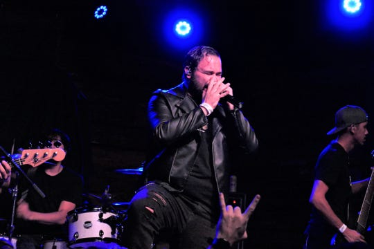 Lead singer of Kingdom Collapse, Jonathan Norris, rocks out at a concert in all black, his favorite clothing.
