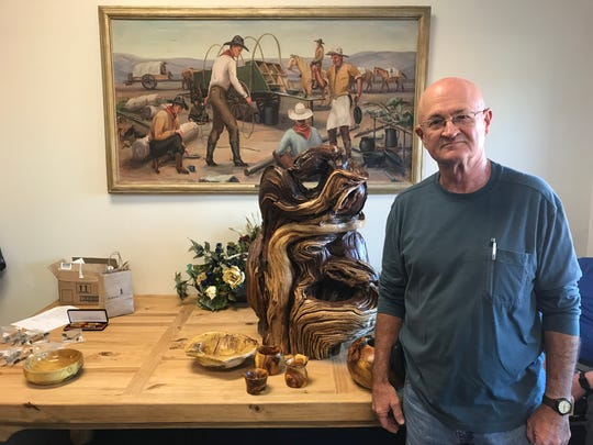 Local wood carver Bobby Farquhar stands next to a free form carving he created using a section of the root ball from the historical bois d'arc tree which was toppled by storms this May after standing on the east side of the county courthouse for more than 135 years.