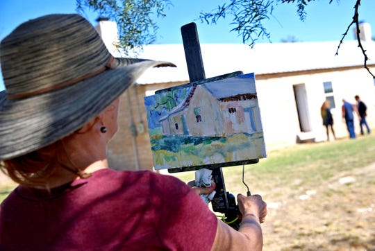 Lorie Merfeld-Batson, left, paints a picture of the Tanskersley Homestead in the background on Saturday, Oct. 19, 2019.