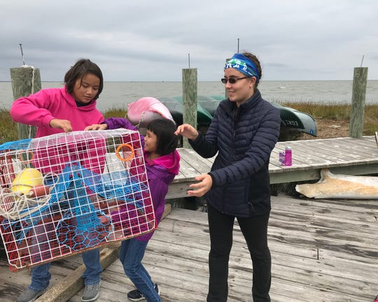 Emily Snyder (left), 15, hands a crab pot to her sister, Evelyn, 11, on the dock at Fox Island in October. Their classmate, Lenka Platt, 18, gets ready to keep the trap moving down the line.