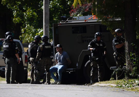 Police take a man into custody following a standoff on East Cairo Street.