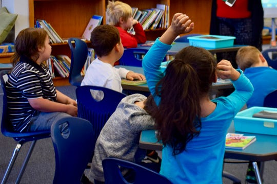 A second grader raises her hand during class in the William Perry Elementary School Library on Oct. 17, 2019.