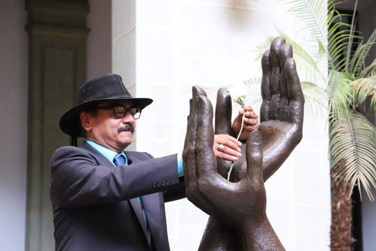 René Corado, of Oxnard, places a white rose in the Monument of Peace after he was honored as an Ambassador of Peace in his native Guatemala in September. Corado is a biologist and the collections manager for the Western Foundation of Vertebrate Zoology in Camarillo.