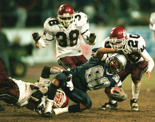 Mt. Whitney defenders #7, #38, and #20 bring down Redwood's #80 during the Cowhide Game in November 2000.