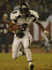 Mt. Whitney's Titus Grayson runs against Redwood. Redwood and Mt. Whitney High School compete in the annual Cowhide game in 2008.