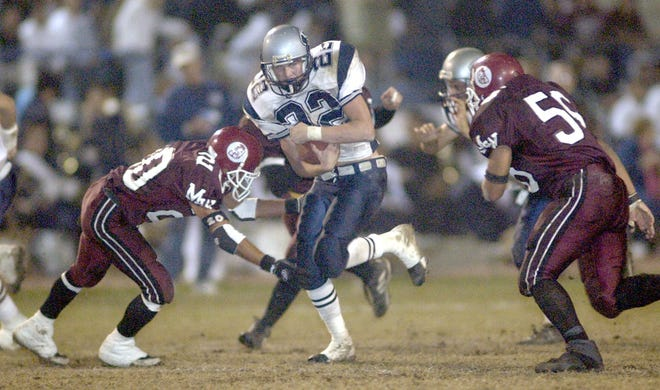 Redwood Rangers running back Andy Infield gets between Mt. Whitney Pioneers' Gabe Contreras, left and Stephen Miranda early during the second quarter of the 47th Annual Cowhide game.