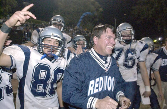 Redwood Rangers varsity football head coach John Yavasile celebrates as the last seconds tick off the clock Friday night at the 47th annual Cowhide game in 1999. Players poured water on him just before the end of the game.