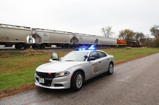 An Ohio State Patrol cruiser sits near the scene where a train struck a car near Adams Mills early Tuesday morning.