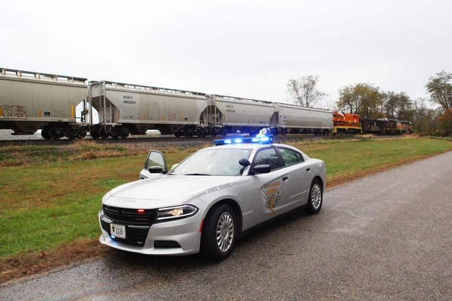 An Ohio State Patrol cruiser sits near the scene where a train struck a car near Adams Mills early Tuesday morning.