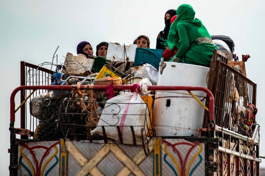 "Syrian Kurdish and Arab families are pictured fleeing in the countryside of the town of Darbasiyah, on the border between Syria and Turkey, towards the town of Hassakeh on October 22, 2019. - Syria's Kurds have withdrawn all their forces from a strip of land bordering Turkey in compliance with a US-brokered truce deal to stem a Turkish assault, a top Kurdish official said. ""We have fully complied with the conditions of the ceasefire agreement,"" Redur Khalil told AFP just hours before a deadline. ""We have withdrawn all our military and security forces from the area of military operations from Ras al-Ain in the east to Tal Abyad in the west,"" he said. (Photo by Delil SOULEIMAN / AFP) (Photo by DELIL SOULEIMAN/AFP via Getty Images) ORIG FILE ID: AFP_1LN3K3"