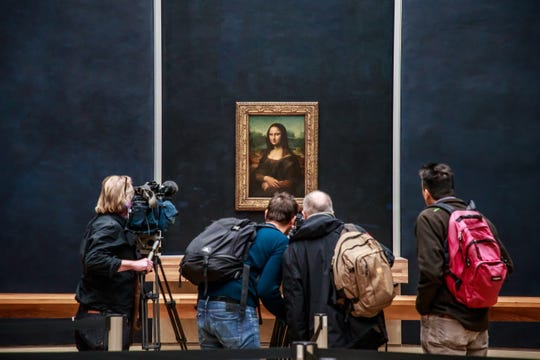 """Journalists crowd around Leonardo's most famous painting, """"Mona Lisa"""" or """"La Gioconda,"""" in its newly renovated room in the Louvre in Paris, on Oct. 22, 2019. The portrait of Lisa Gherardini, wife of Francesco del Giocondo, is believed to have been painted between 1503 and 1506 and is one of the Louvre's most prized artworks."""